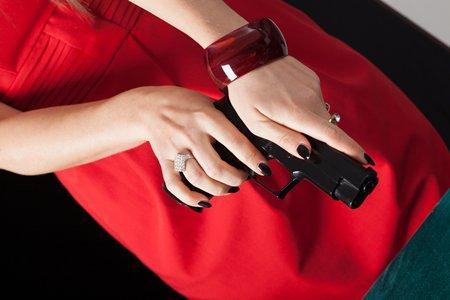 Woman in red dress reloading pistol